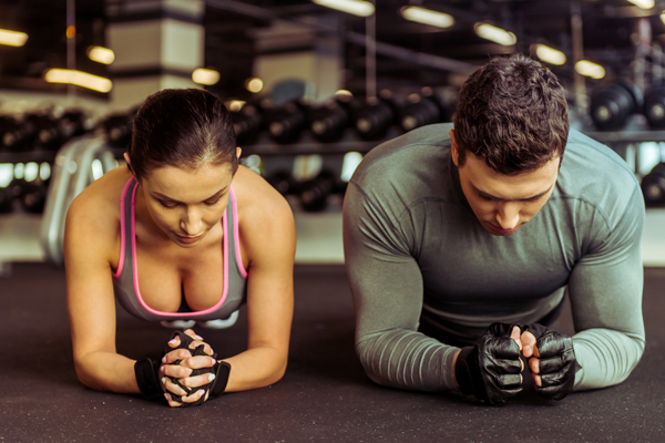 Attractive young muscular man and woman doing plank exercise while working out in gym