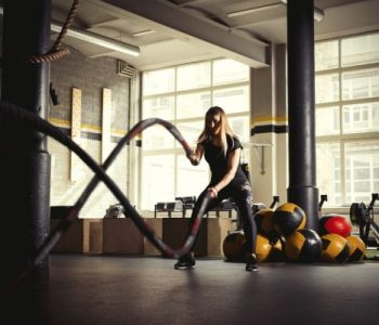 Woman training with battle ropes in gym