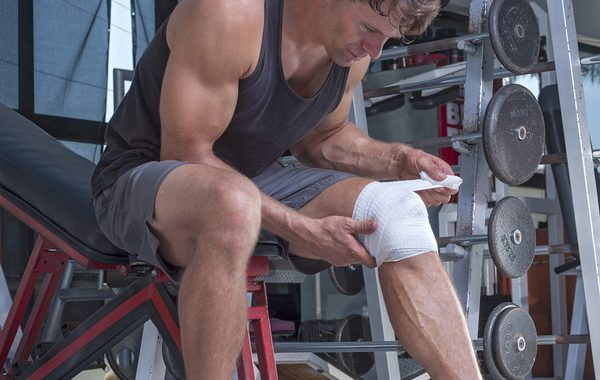 Muscular Caucasian man wraps knee with sport bandage in weightlifting gym