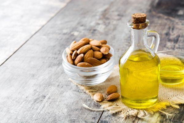 Almond oil in bottle on wooden table