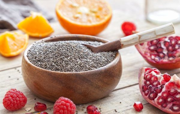 Chia seeds in a bowl surrounded by fruit on a vintage wooden table